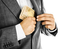 A businessman in a suit putting money in his pocket Stock Photos