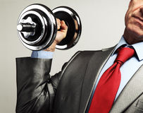 Businessman in suit raising dumbbell. Tax burden concep Stock Photo