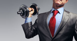 Businessman in suit raising dumbbell. Tax burden concept Royalty Free Stock Photos