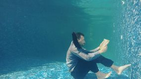 Businessman in suit read book under water. Underwater. Businessman in suit slowly moves under water with book in hands. Handsome bearded guy read the book and stock footage