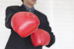 Businessman in suit with red boxing gloves punch to you Stock Images