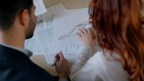 Businessman in suit and red hair female financial analytic researching market trends. On printed graphs in the office. Indoors. Back view stock video footage