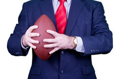 Businessman in suit, red tie holding a football Royalty Free Stock Photography
