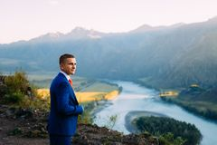 Businessman in a suit with red tie on the top of the world with background of mountains and river. Alps stock photos