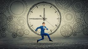 Run on time. Businessman in suit running on time. Jump over clock sketch surrounded by gears cog wheels. Business time management concept stock photos