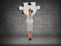 Businessman in suit setting piece of puzzle Stock Images