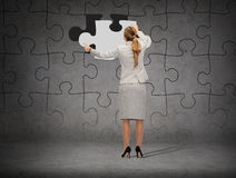 Businessman in suit setting piece of puzzle Stock Photography