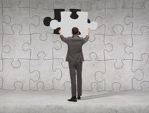 Businessman in suit setting piece of puzzle Stock Image
