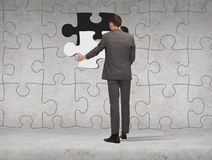 Businessman in suit setting piece of puzzle Royalty Free Stock Photo