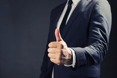Businessman in suit showing Good sign with his thumb up on black. Background Royalty Free Stock Image