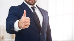 Businessman in suit showing thumb up, crop stock photo