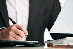 Businessman in a suit signing or writing a document agreement. Close up of the hands of a businessman in a suit signing or writing a document agreement on a Royalty Free Stock Images