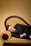 Businessman in suit sleeping on sofa in room Royalty Free Stock Photography
