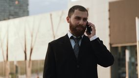 Businessman in suit speaking on mobile telephone on modern building background. stock video footage