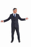 Businessman in suit spreading his arms Stock Image