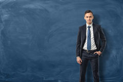 Businessman in suit standing and confidently looking forward with his hand in pocket Royalty Free Stock Image
