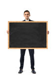 Businessman in suit standing and holding blackboard in wooden frame, isolated on white background Royalty Free Stock Image