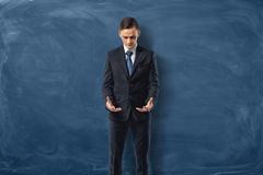 Businessman in suit standing and looking at his empty hands on dark blue background. Royalty Free Stock Photography