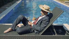 Businessman in suit and in straw hat works with tablet near swimming pool stock video footage