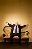 Businessman in suit stretches after dream on sofa royalty free stock image
