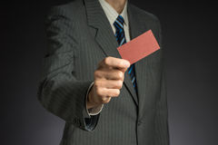 Businessman with suit stretching arm, red business card in hand. Gray background Stock Photography