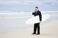 Businessman in suit with surfboard on the beach Royalty Free Stock Images