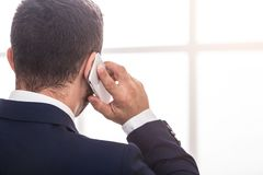 Businessman in suit talking on mobile phone, back view stock photos