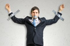 Businessman in suit is taped to the wall with adhesive tape.  stock photography