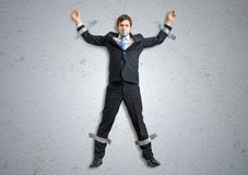 Businessman in suit is taped to the wall with adhesive tape.  royalty free stock photo