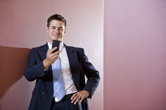 Businessman in suit texting in hallway stock image