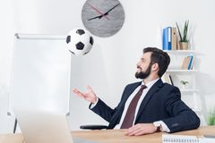 Businessman in suit throwing soccer ball at workplace. In office stock photography