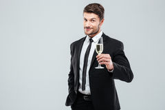 Businessman in suit and tie cheers with glass of champagne Stock Photos