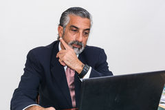 Businessman in suit and tie, concentrated, in his studio. Royalty Free Stock Photography