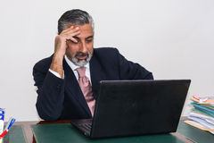 Businessman in suit and tie, concentrated, in his studio. Stock Photography