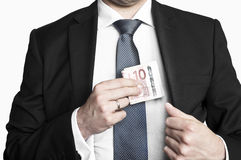 Businessman in suit and tie hiding money in his pocket. Businessman wearing suit and tie hiding money in his pocket Royalty Free Stock Image