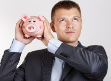 Businessman in suit and tie shaking funny piggybank Stock Photos