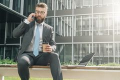 Businessman in suit and tie is sitting outside on bench, drinking coffee and talking on his cell phone. Nearby is laptop. Young businessman in suit and tie is Stock Photography