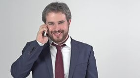 Businessman in suit with tie smiling and talking on the phone stock video