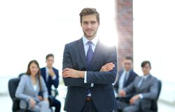 Successful businessman at the office leading a group. Businessman in a suit and tie standing in a modern office building with his arms crossed in front of out royalty free stock images