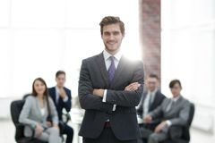 Successful businessman at the office leading a group. Businessman in a suit and tie standing in a modern office building with his arms crossed in front of out Royalty Free Stock Image