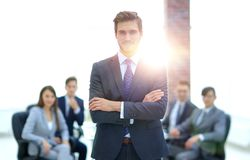 Successful businessman at the office leading a group. Businessman in a suit and tie standing in a modern office building with his arms crossed in front of out Stock Photos
