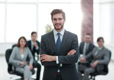 Successful businessman at the office leading a group. Businessman in a suit and tie standing in a modern office building with his arms crossed in front of out stock photo