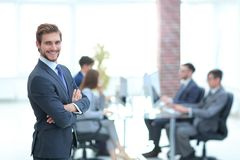 Successful businessman at the office leading a group. Businessman in a suit and tie standing in a modern office building with his arms crossed in front of out stock photography