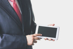 Businessman. In suit and tie using a tablet Royalty Free Stock Image