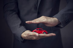 Businessman in suit with two hands in position to protect a car. (focus on hand, blur out the suit). It indicates many aspects such as car insurance coverage Stock Photos