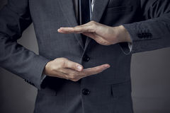 Businessman in suit with two hands in position to protect something. (focus on hand, blur out the suit). It indicates many aspects such as car insurance Royalty Free Stock Photos