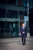 Businessman in suit walking outdoors office. Businessman walking outdoors in front of a modern office building Stock Photography