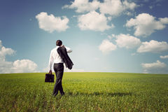 Businessman in a suit walking on a spacious green field. Businessman in a suit with a briefcase walking on a spacious green field with a blue sky Stock Photo