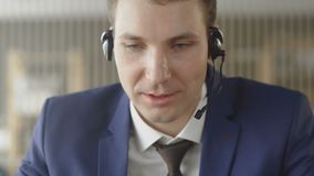 Businessman in suit wear headset talking looking at laptop making notes, male customer support manager skyping on