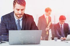Businessman in a suit working at office desk in front of laptop while two other collegues behind are discussing project. Concept royalty free stock photography